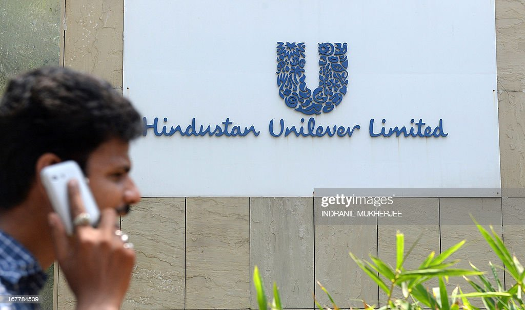 A pedestrian talks on his mobile phone as he walks past the logo of Hindustan Unilever Limited outside its office in Mumbai on April 30, 2013. Food giant Unilever on Tuesday announced a 5.4-billion dollar offer to raise its stake in its Indian subsidiary, eyeing explosive sales of branded consumer items to the Asian country's growing middle class. The Anglo-Dutch firm made an offer to buy another 22.5 percent of already majority-owned Hindustan Unilever (HUL) in a proposed deal that would increase its control to 75 percent.