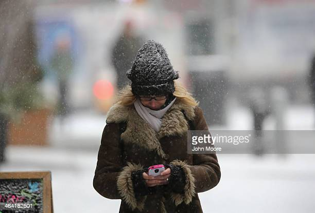 A pedestrian types on her smartphone during a snowstorm on January 21 2014 in New York City Areas of the Northeast are predicted to receive up to a...