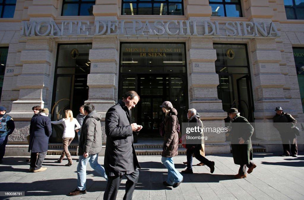 A pedestrian uses a mobile device as he passes a Banca Monte dei Paschi di Siena SpA bank branch in Rome, Italy, on Friday, Jan. 25, 2013. Italian Prime Minister Mario Monti said the Bank of Italy will take another look at Banca Monte dei Paschi di Siena SpA's books after the company disclosed this week it may face more than 700 million euros of losses related to structured finance transactions hidden from regulators. Photographer: Alessia Pierdomenico/Bloomberg via Getty Images