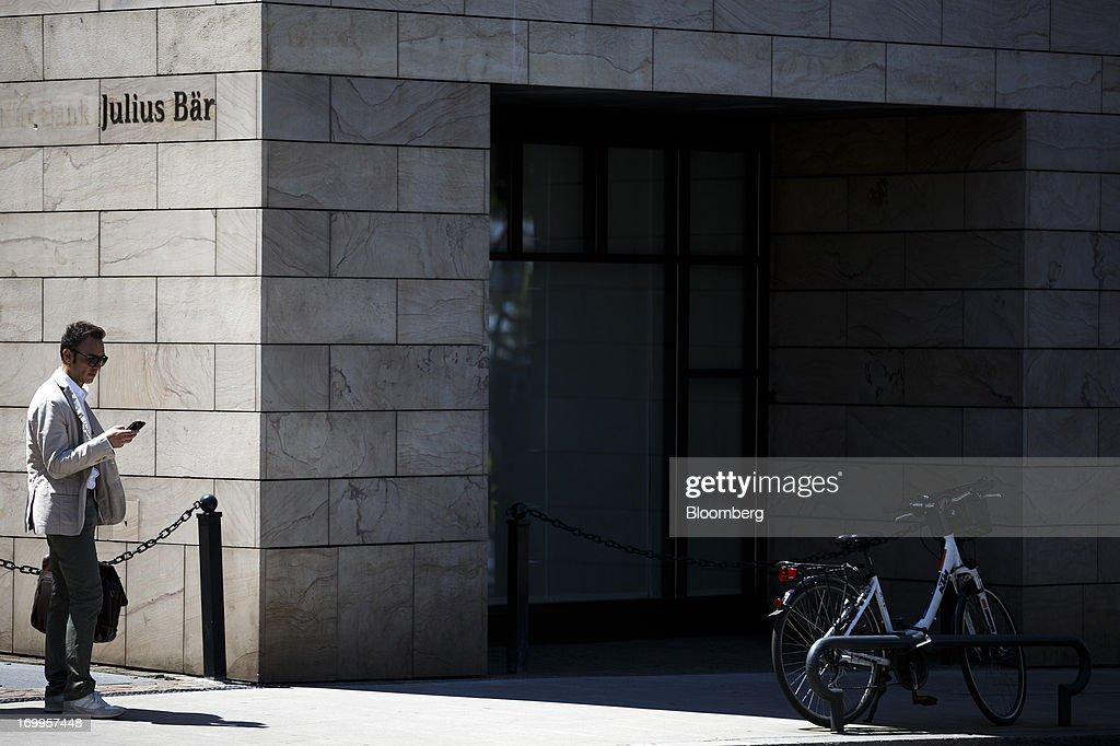 A pedestrian uses a mobile device as he passes the offices of Julius Baer Group Ltd. in Geneva, Switzerland, on Wednesday, June 5, 2013. Members of the Swiss parliament's upper house's economic committee have been debating a law which, if passed, could authorize Swiss banks to cooperate with U.S. authorities. Photographer: Valentin Flauraud/Bloomberg via Getty Images