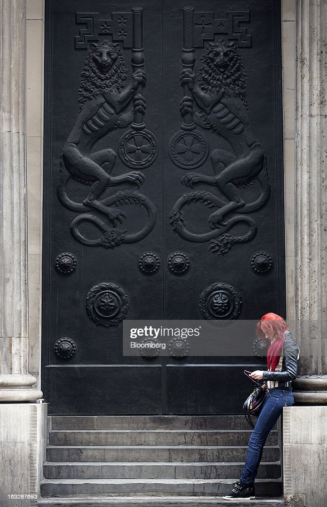 A pedestrian uses a mobile device as she waits outside a doorway at the Bank of England (BoE) in London, U.K., on Thursday, March 7, 2013. The pound dropped to its weakest level in more than 2 1/2 years versus the dollar before Bank of England policy makers announce their decision on whether they will add more stimulus to boost the U.K. economy. Photographer: Simon Dawson/Bloomberg via Getty Images
