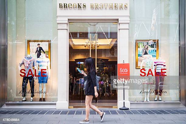 A pedestrian uses a mobile device as she walks past sale signs in a Brooks Brothers Inc store on Orchard Road in Singapore on Sunday June 21 2015...