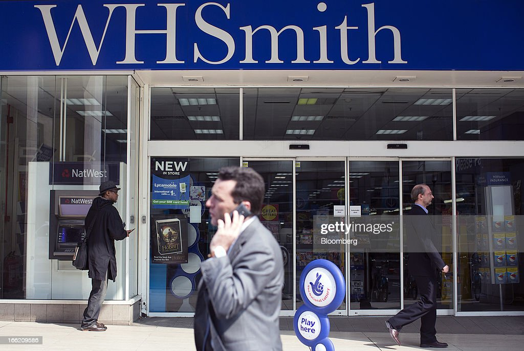 A pedestrian uses a mobile handset as he passes the entrance to a WH Smith Plc store in London, U.K., on Wednesday, April 10, 2013. WH Smith Plc, the book and magazine retailer with more than 1,100 U.K. outlets, is scheduled to announce earnings on April 11. Photographer: Simon Dawson/Bloomberg via Getty Images