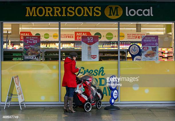 A pedestrian uses a mobile handset as she stands with a baby stroller outside a Morrisons M Local store operated by Wm Morrison Supermarkets Plc in...