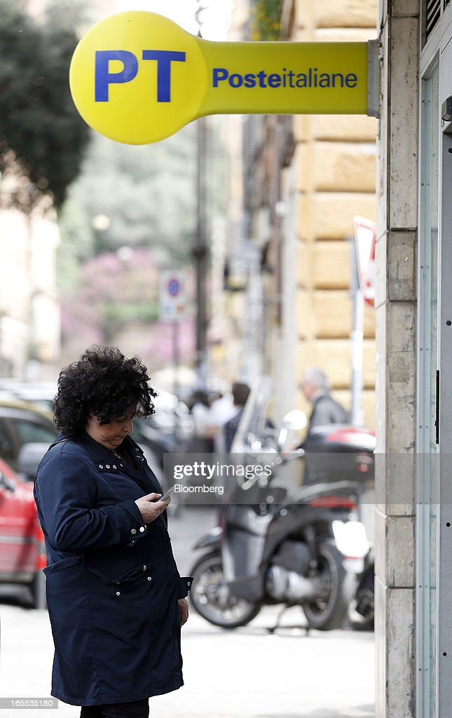 A pedestrian uses a mobile handset outside the entrance to a Poste Italiane SpA post office in Rome, Italy, on Thursday, April 4, 2013. Italy's state-owned postal service and Wind SpA, the country's third-largest mobile-phone company, are discussing a possible venture with Wind's fixed-line network Infostrada, Poste Italiane SpA Chief Executive Officer Massimo Sarmi said. Photographer: Alessia Pierdomenico/Bloomberg via Getty Images