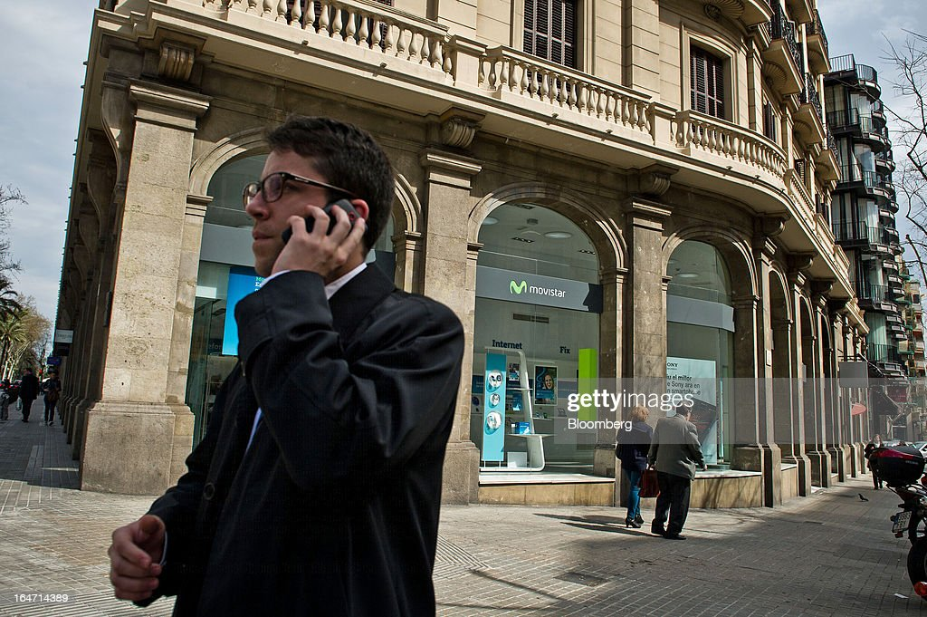 A pedestrian uses a mobile handset while passing a Telefonica SA phone store in Barcelona, Spain, on Tuesday, March 26, 2013. Telefonica, seeking to reduce net debt by more than 4 billion euros this year, is following companies such as Repsol SA, Spain's biggest oil company, and builder Actividades de Construccion & Servicios SA, to sell treasury shares. Photographer: David Ramos/Bloomberg via Getty Images