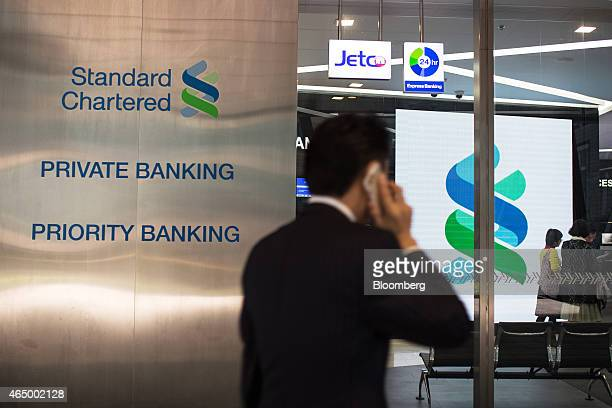 A pedestrian uses a mobile phone as he walks past a Standard Chartered Plc bank branch in the Central district of Hong Kong China on Monday March 2...