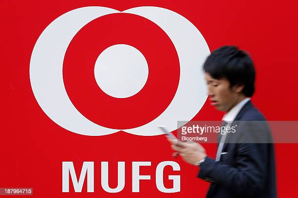 A pedestrian uses a mobile phone as he walks past the corporate logo of Mitsubishi UFJ Financial Group Inc outside a branch of Bank of Tokyo...