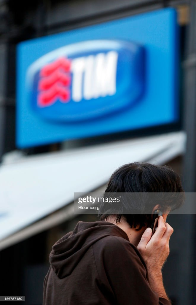 A pedestrian uses a mobile phone outside a TIM store, the mobile unit of Telecom Italia SpA, in Milan, Italy, on Tuesday, Nov. 20, 2012. Telecom Italia SpA said it is still reviewing the possible spinoff of its fixed-line network and the company's board will discuss the outcome of its analysis on Dec. 6. Photographer: Alessia Pierdomenico/Bloomberg via Getty Images