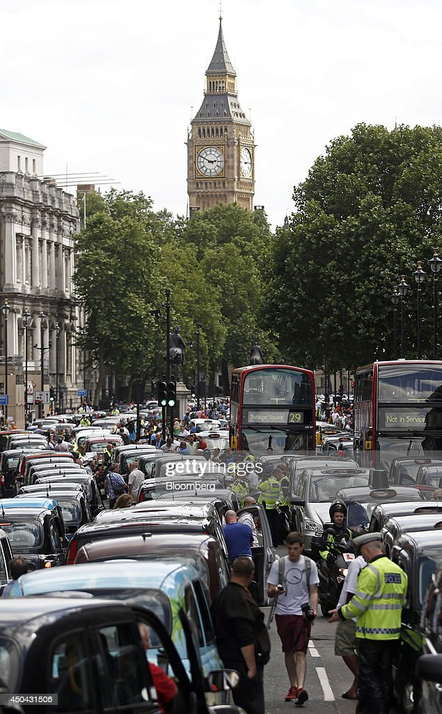 A pedestrian uses a smartphone as he walks between lines of London taxi cabs parked on Whitehall, near Big Ben and the Houses of Parliament, during a protest against Uber Technologies Inc.'s car sharing service in London, U.K., on Wednesday, June 11, 2014. Traffic snarled in parts of Madrid and Paris today, with a total of more than 30,000 taxi and limo drivers from London to Berlin blocking tourist centers and shopping districts. Photographer: Simon Dawson/Bloomberg via Getty Images
