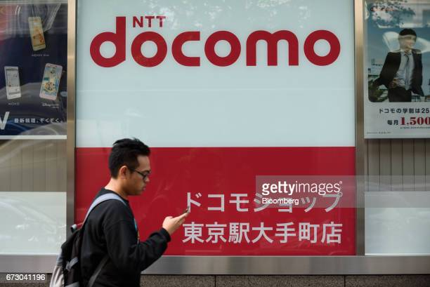 A pedestrian uses a smartphone as he walks past an NTT Docomo Inc store in Tokyo Japan on Monday April 24 2017 NTT Docomo one of the world's largest...