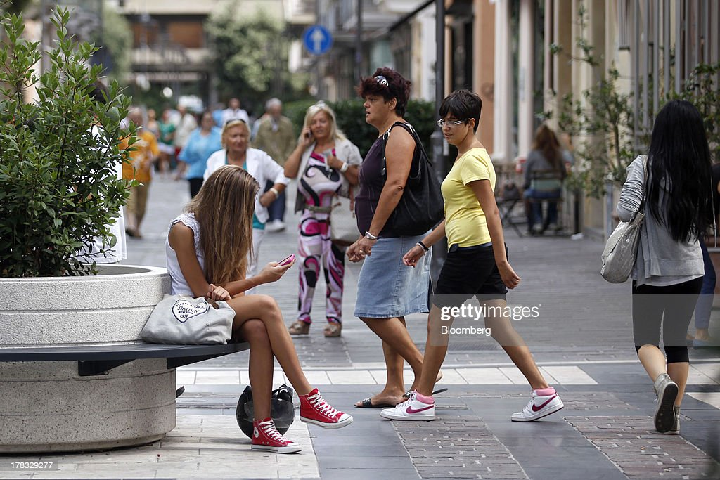 A pedestrian uses a smartphone as she sits on a bench near shops and restaurants in Pescara, Italy, on Thursday, Aug. 29, 2013. Italian consumer confidence rose this month more than economists expected as households grew optimistic amid expectations that the government would cut a property tax. Photographer: Marc Hill/Bloomberg via Getty Images