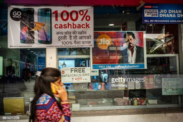 A pedestrian uses a smartphone while walking past advertising for Reliance Jio Infocomm Ltd displayed in the window of a store at the Nehru Place IT...