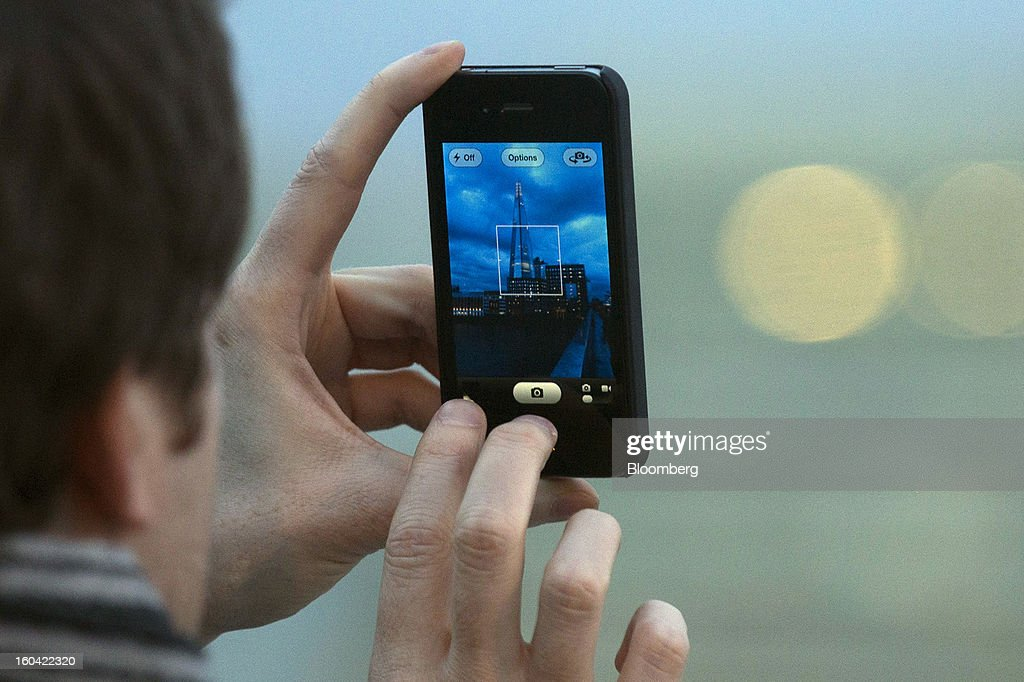 A pedestrian uses an Apple Inc. iPhone to take a photograph of the Shard tower in London, U.K., on Thursday, Jan. 31, 2013. The Shard, which stands at 309.6 meters on London's South Bank, opens to the public on Feb. 1, and is owned by LBQ Ltd., which brings together the State of Qatar (the majority shareholder) and Sellar Property Group Ltd., with non-equity funding by Qatar National Bank. Photographer: Simon Dawson/Bloomberg via Getty Images