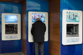 A pedestrian uses an automated teller machine on a street in Istanbul Turkey on Sunday Jan 5 2014 The Turkish lira is poised to rebound after a...