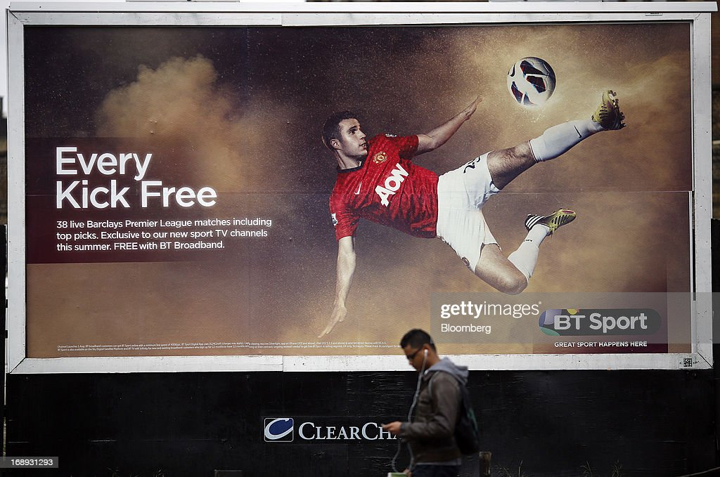 A pedestrian uses an personal electronic device as he passes a billboard advertisement for BT Group Plc's new sports television service BT Sport in London, U.K. on Friday, May 17, 2013. BT Group Plc said it will offer its new BT Sport channels free with broadband subscriptions to make its bundles of phone, Internet and TV service more appealing. Photographer: Simon Dawson/Bloomberg via Getty Images