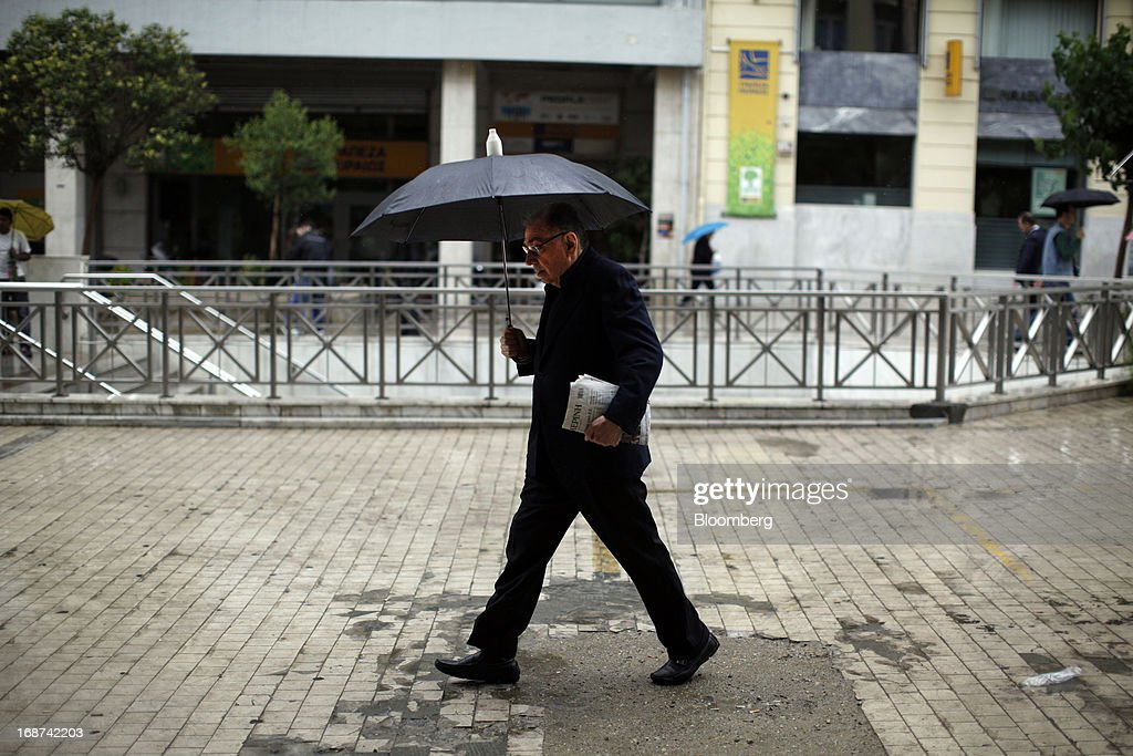 A pedestrian uses an umbrella to shelter from the rain while walking in central Athens, Greece, on Tuesday, May 14, 2013. Greek Prime Minister Antonis Samaras said the country can beat the targets set under its 240 billion-euro ($311 billion) International Monetary Fund and euro area bailout program and return to bond markets in the first half of next year. Photographer: Kostas Tsironis/Bloomberg via Getty Images