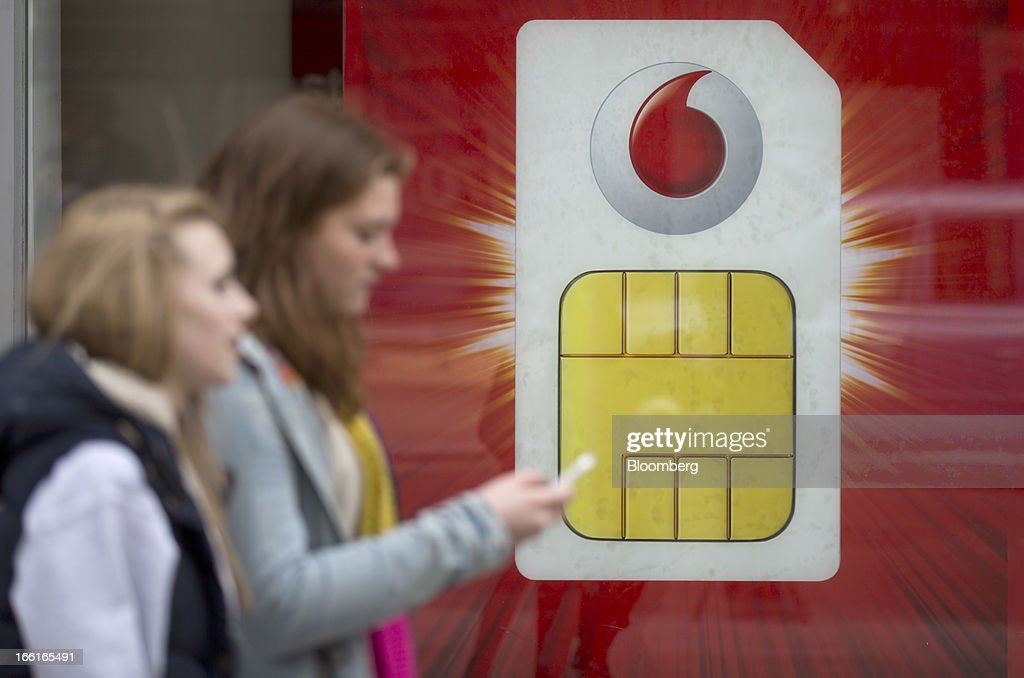 A pedestrian uses her mobile handset as she passes an advert in the window display of a Vodafone Group Plc store on Oxford Street in London, U.K., on Monday, April 8, 2013. Vodafone Group Plc is restating its results going back two fiscal years as new international accounting rules for joint ventures cut historical revenue and earnings. Photographer: Simon Dawson/Bloomberg via Getty Images