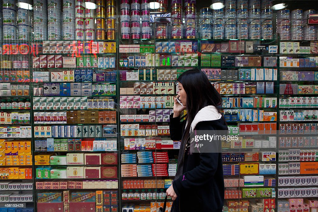 A pedestrian uses her mobile phone as she walks past a shop front in Hong Kong on December 20, 2013. Australian telecommunications giant Telstra on December 20 announced the sale of its Hong Kong-based mobile business CSL to HKT Limited for 2.42 billion USD.