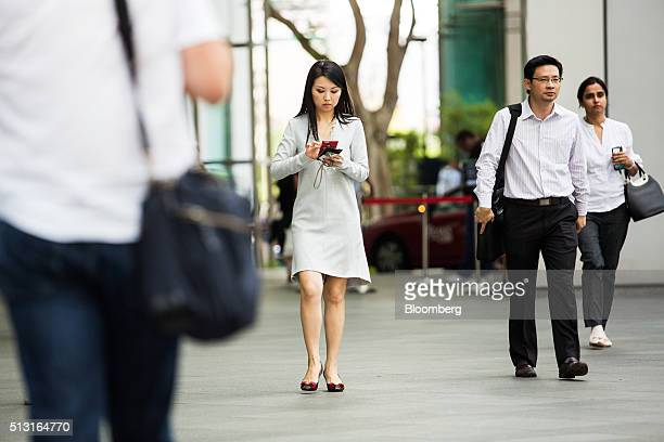 A pedestrian uses her mobile phone at Raffles Place in the central business district area of Singapore on Monday Feb 29 2016 Singapore's Infocomm...