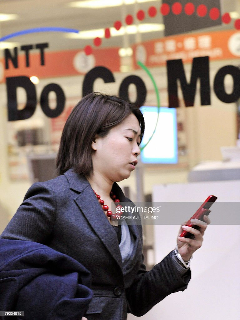 A pedestrian uses her mobile phone before a NTT DoCoMo shop in Tokyo 29 January 2008 Japan's largest mobile telephone operator NTT DoCoMo said its...