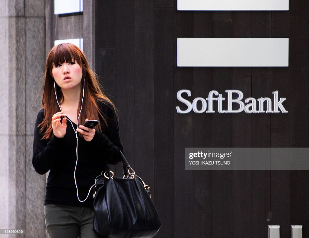 A pedestrian uses her mobile phone before a Softbank mobile phone shop in Tokyo on October 12, 2012. Japanese mobile carrier Softbank is eyeing a monster 25 billion USD buy-in to the US telecom market including the takeover of Sprint Nextel in what could be among Japan Inc.'s biggest-ever overseas deals. Sprint Nextel confirmed it was talking with Softbank about a takeover, which could help vault the Japanese firm into the top three mobile giants globally. AFP PHOTO / Yoshikazu TSUNO