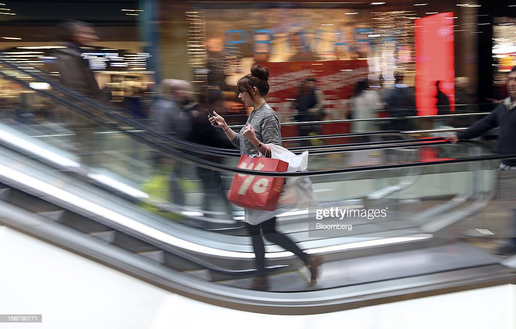 A pedestrian uses her mobile phone whilst carrying branded shopping bags inside the Westfield Stratford City shopping mall in London, U.K., on Thursday, Dec. 27, 2012. Overall Christmas shopping in the U.K. was similar to last year, according to the British Retail Consortium. Photographer: Chris Ratcliffe/Bloomberg via Getty Images