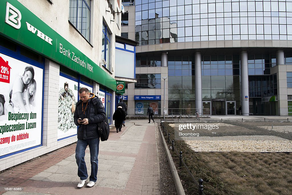 A pedestrian uses his mobile handset as he passes a Bank Zachodni WBK SA branch in Wroclaw, Poland, on Monday, March 25, 2013. KBC Groep NV of Belgium and Banco Santander SA of Spain raised 4.89 billion zloty ($1.51 billion) from the sale of a stake in Bank Zachodni WBK SA, Poland's third-largest lender. Photographer: Bartek Sadowski/Bloomberg via Getty Images