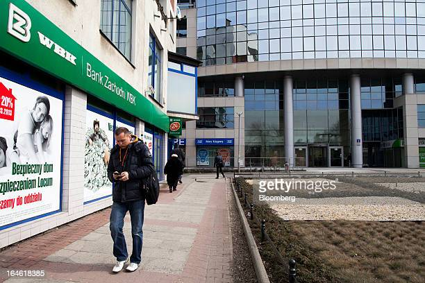 A pedestrian uses his mobile handset as he passes a Bank Zachodni WBK SA branch in Wroclaw Poland on Monday March 25 2013 KBC Groep NV of Belgium and...
