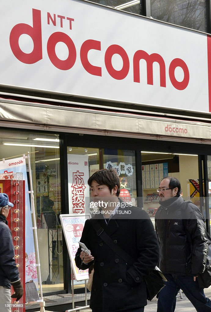 A pedestrian uses his mobile phone as he walks past shop of Japan's mobile communication giant NTT DoCoMo in Tokyo on January 27 2012 NTT DoCoMo...