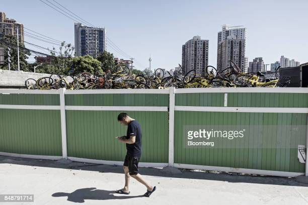 A pedestrian uses his mobile phone while walking past a pile of ridesharing bicycles behind a fence in Shanghai China on Thursday Sept 12 2017 Across...