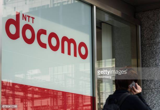 A pedestrian uses his smartphone as he walks past an NTT Docomo Inc store in Tokyo Japan on Monday April 24 2017 NTT Docomo is scheduled to release...