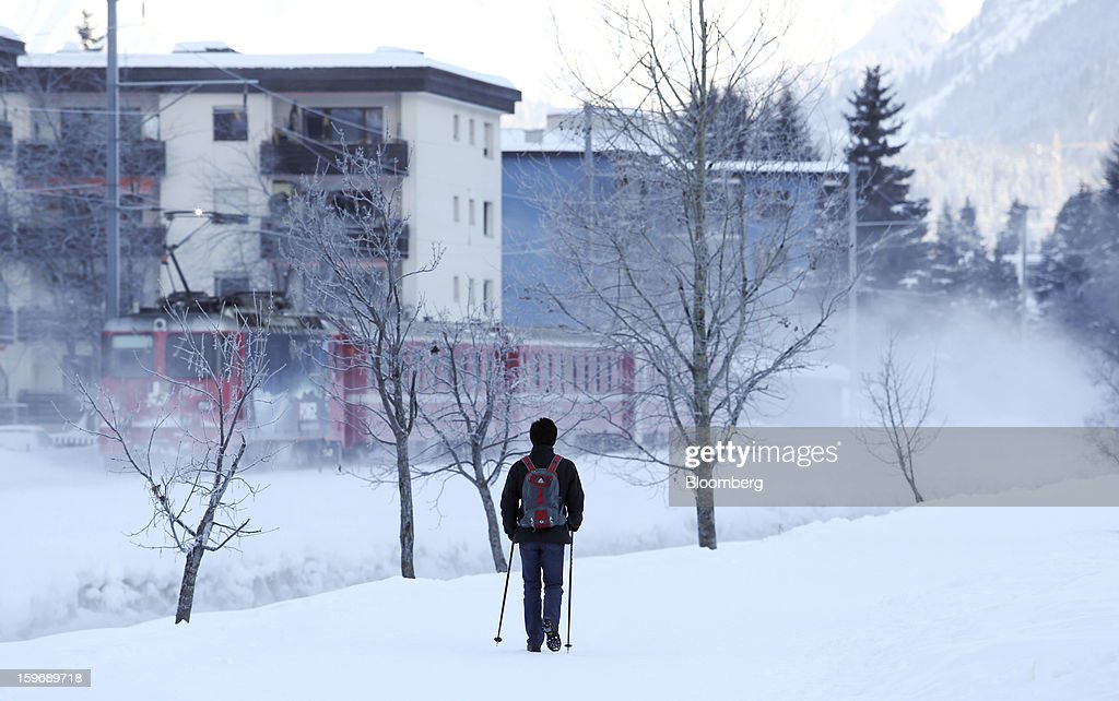 A pedestrian uses ski poles as he walks near the main railway line in Davos, Switzerland, on Friday, Jan. 18, 2013. Next week the business elite gather in the Swiss Alps for the 43rd annual meeting of the World Economic Forum in Davos, the five day event runs from Jan. 23-27. Photographer: Chris Ratcliffe/Bloomberg via Getty Images