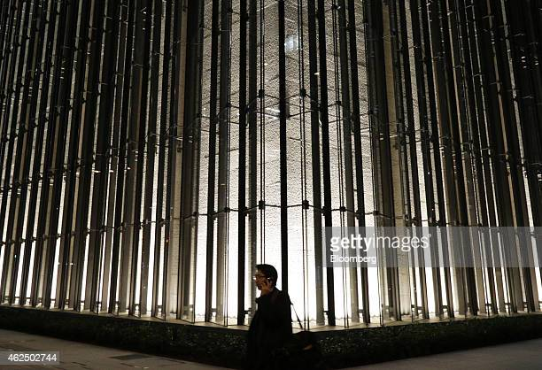 A pedestrian using a mobile phone walks past the Mizuho Financial Group Inc headquarters in Tokyo Japan on Thursday Jan 29 2015 Mizuho Financial...