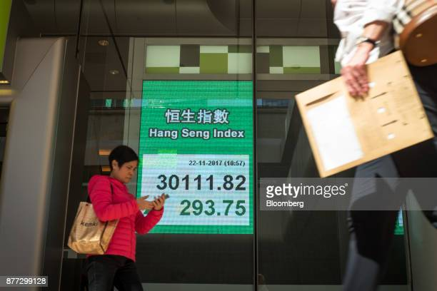 A pedestrian using a smart phone walks past an electronic screen displaying the Hang Seng Index in Hong Kong China on Wednesday Nov 22 2017 Hong...