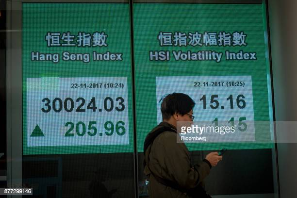 A pedestrian using a smart phone walks past an electronic screen displaying the Hang Seng Index left and the HSI Volatility Index in Hong Kong China...