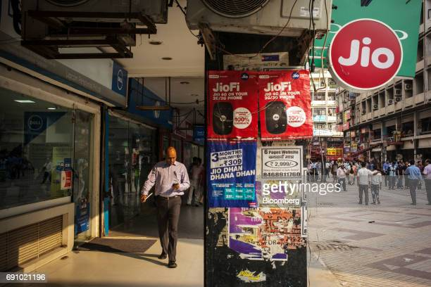 A pedestrian using a smartphone walks past advertising and signage for Reliance Jio Infocomm Ltd at the Nehru Place IT Market in New Delhi India on...