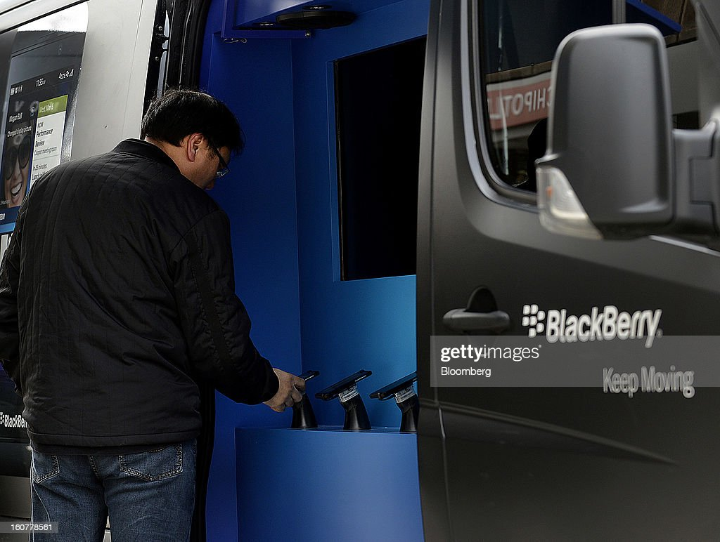A pedestrian views a BlackBerry Z10 device displayed at a mobile kiosk on Yonge Street during the first day of sales in Toronto Ontario Canada on...