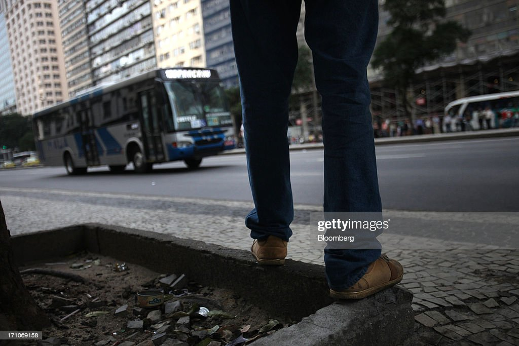 A pedestrian waits for a bus on Presidente Getulio Vargas Avenue in Rio de Janeiro, Brazil, on Friday, June 21, 2013. Brazils swelling street rebellion claimed its second fatality in the largest and most violent protests yet, as 1 million demonstrators rallied for better public services and an end to corruption. Photographer: Dado Galdieri/Bloomberg via Getty Images