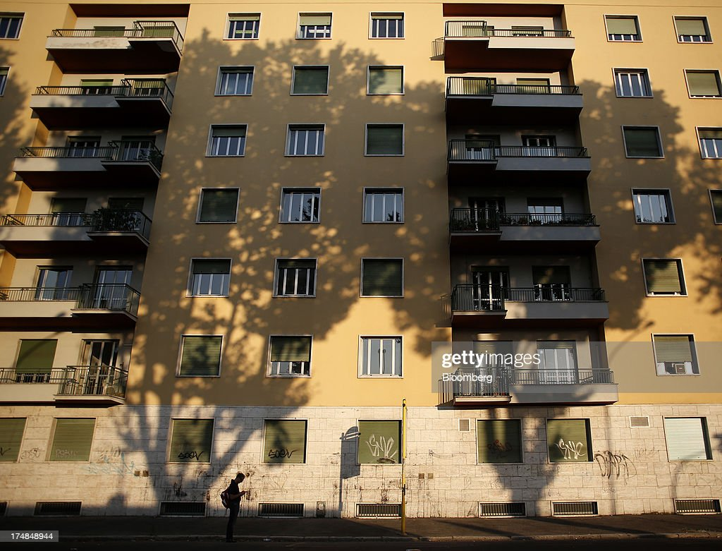 A pedestrian waits for transportation at a bus stop in front of a residential apartment block in Rome, Italy, on Saturday, July 27, 2013. Italy's home prices are low enough to trigger an increase in purchases for the first time since 2006, though that won't lift values for at least two years, according to the Nomisma institute. Photographer: Alessia Pierdomenico/Bloomberg via Getty Images