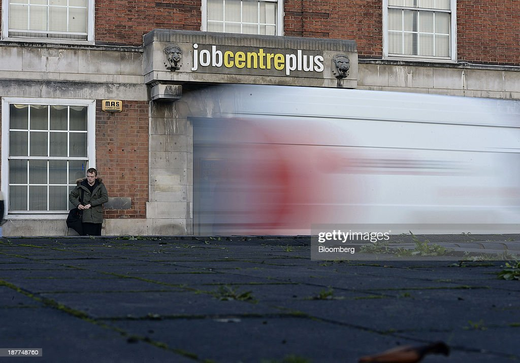 A pedestrian waits outside a job centre in Leeds, U.K., on Tuesday, Nov. 12, 2013. Under Bank of England Governor Mark Carney's forward-guidance policy, the central bank has pledged to not to withdraw stimulus at least until unemployment falls to 7 percent. Photographer: Nigel Roddis/Bloomberg via Getty Images