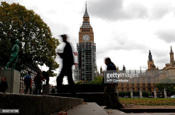 Pedestrian walk in Parliament Square as workmen continue to erect scaffolding around the Elizabeth Tower commonly known as Big Ben during ongoing...