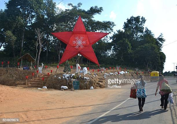 Pedestrian walk pass a giant Christmas star put up on a road side ahead of Christmas celebration at Indesen Colony in Dimapur India north eastern...