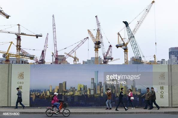 Pedestrian walk past a construction site in Beijing on April 1 2015 China's manufacturing activity expanded in March for the first time since...