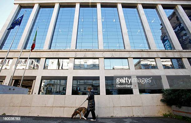 A pedestrian walks a dog past the Banca d'Italia Italy's central bank in Rome Italy on Friday Jan 25 2013 Italian Prime Minister Mario Monti said the...