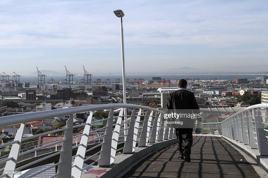 A pedestrian walks across a bridge toward the Woodstock residential district in Cape Town, South Africa, on Wednesday, April 24, 2013. South Africa's gross domestic product is forecast to expand 2.6 percent this year, compared with 2.5 percent in 2012, according to the country's central bank. Photographer: Nadine Hutton/Bloomberg via Getty Images