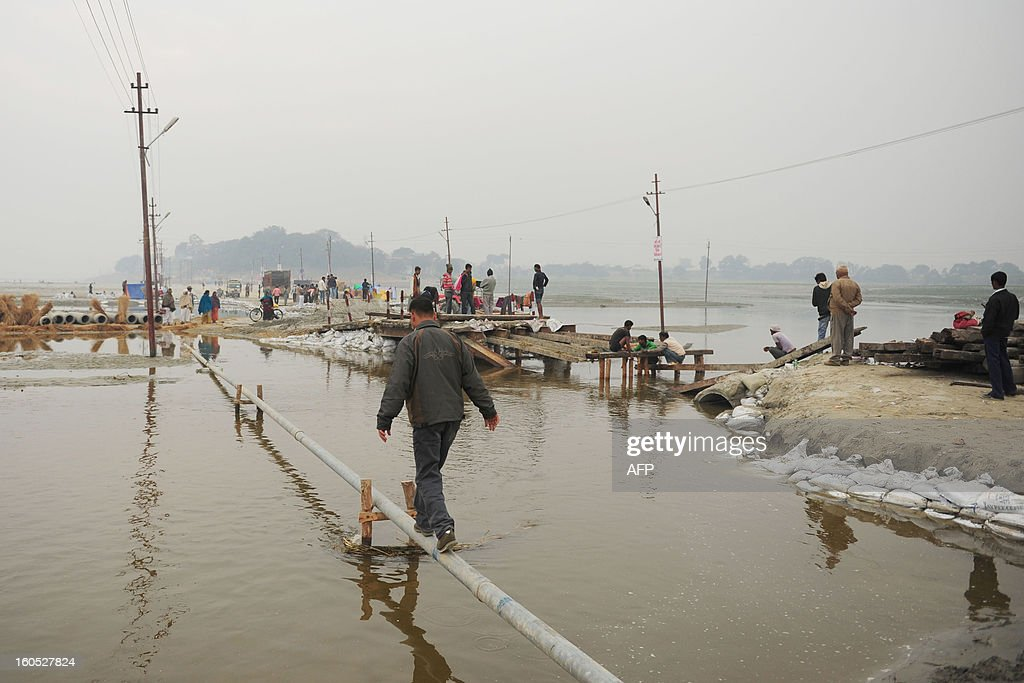 A pedestrian walks across a narrow pipe to cross a section of the River Ganges following the closure of a nearby pontoon bridge during the Maha Kumbh festival, in Allahabad on February 2, 2013. The Kumbh Mela in the town of Allahabad will see up to 100 million worshippers gather over 55 days to take a ritual bath in the holy waters, believed to cleanse sins and bestow blessings. AFP PHOTO/Sanjay KANOJIA