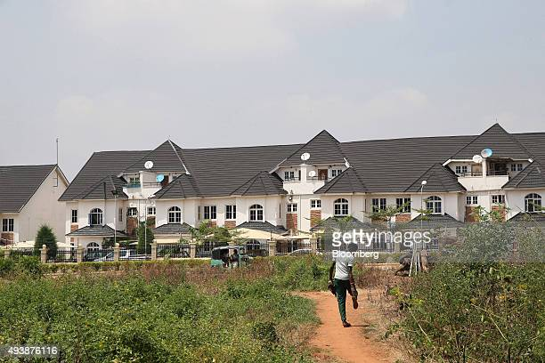 A pedestrian walks along a dirt path towards a newly completed residential housing estate in Abuja Nigeria on Wednesday Oct 21 2015 A drop in crude...