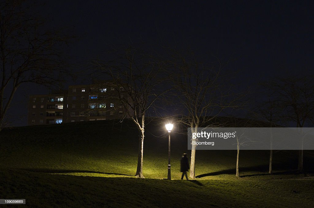 A pedestrian walks along a path illuminated by an electric street light in a park in Madrid, Spain, on Sunday, Jan. 6, 2013. In December, the Spanish parliament passed an energy law that imposed a 7 percent tax on electricity generation from Jan. 1 to plug the deficit. Photographer: Angel Navarrete/Bloomberg via Getty Images