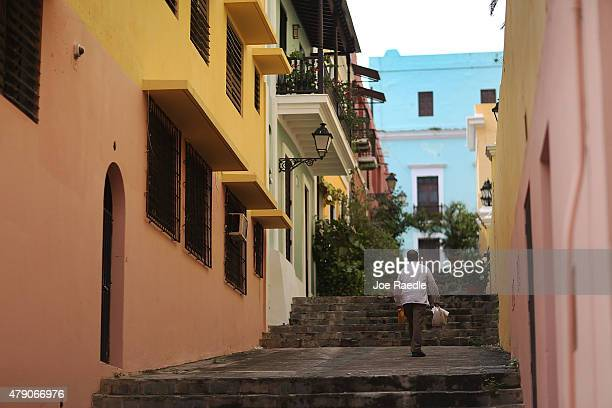 A pedestrian walks along a street in Old San Juan a day after the Puerto Rican Governor Alejandro Garcia Padilla gave a televised speech regarding...